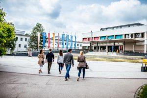 Studierende gehen über den Campus zum Haupteingang der Universität Klagenfurt