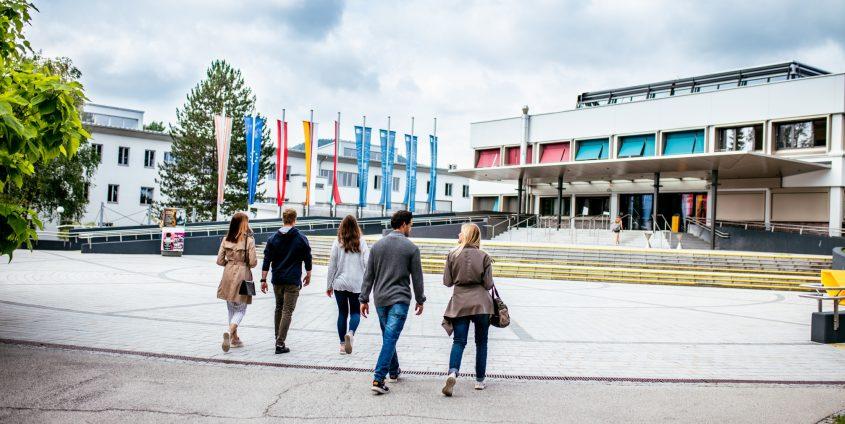 Studierende gehen über den Campus der Universität Klagenfurt