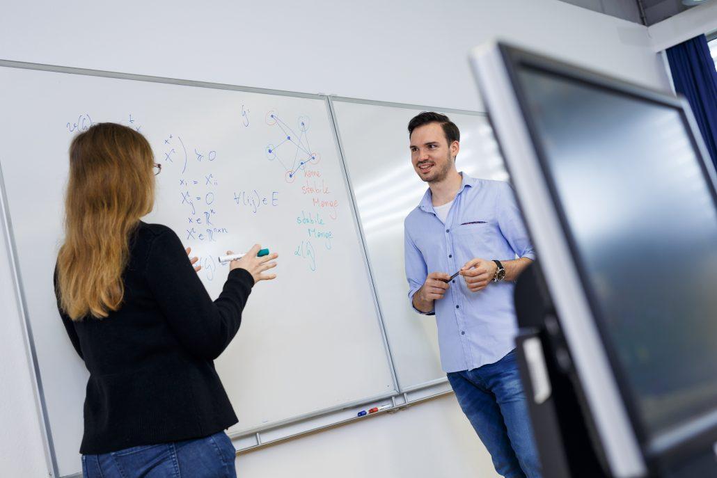 Lehrende arbeitet mit Studierendem am Whiteboard