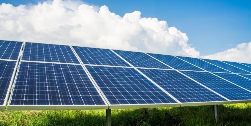 Photovoltaikmodule in Grünfläche mit Himmel und Wolken