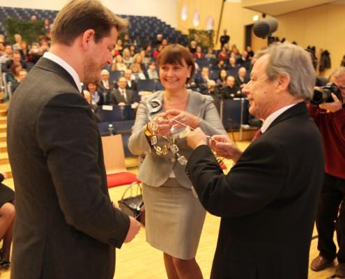 Senatsvorsitzender Norbert Frei und Universitätsratsvorsitzende Herta Stockbauer legen Oliver Vitouch die Rektorskette um   Foto: aau/Hoi