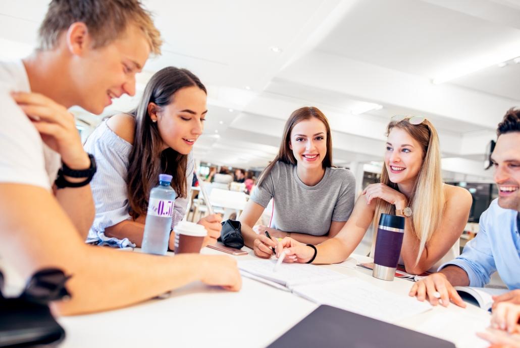 Studierende an einem Tisch in der Aula
