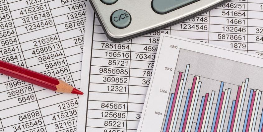 Ein Taschenrechner liegt auf den Zahlen einer Bilanz und Statistik. Symbolphoto