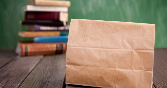 Paper lunch bag for school on wooden table
