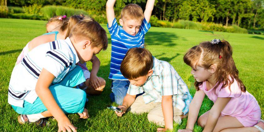 Kindergartenkinder suchen mit Lupe im Graf