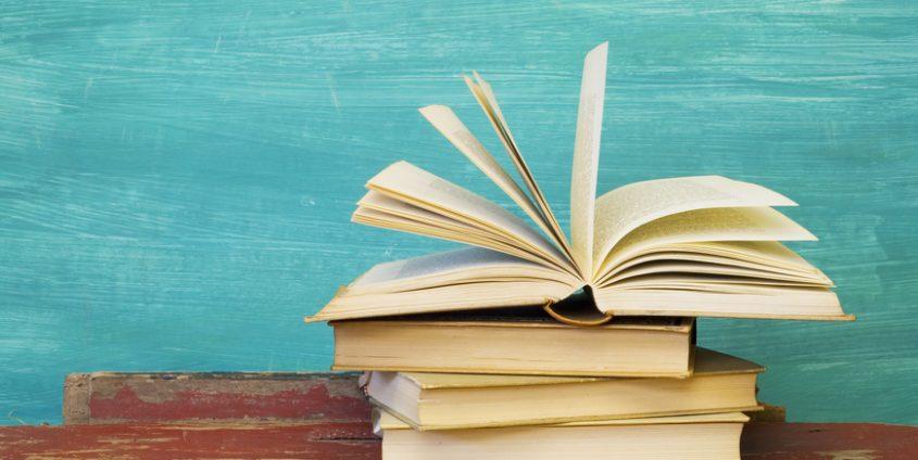 Bücherstapel vor türkisem Hintergrund