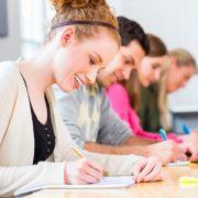 Junge Frau schreibt in Schulbank