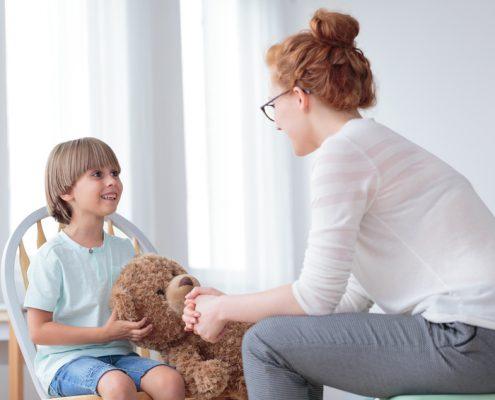 Kinderpsychologin mit Jungem und Teddybär