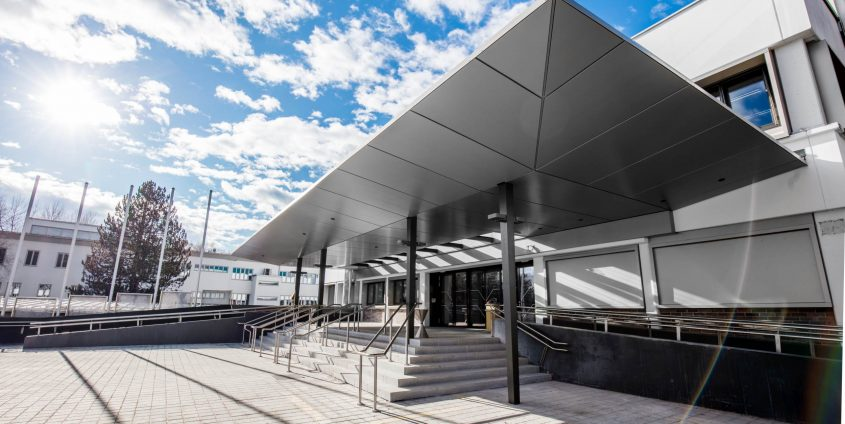 Mit dem Vordach aus Metall bekommt der Haupteingang ein offenes und modernes Gesicht