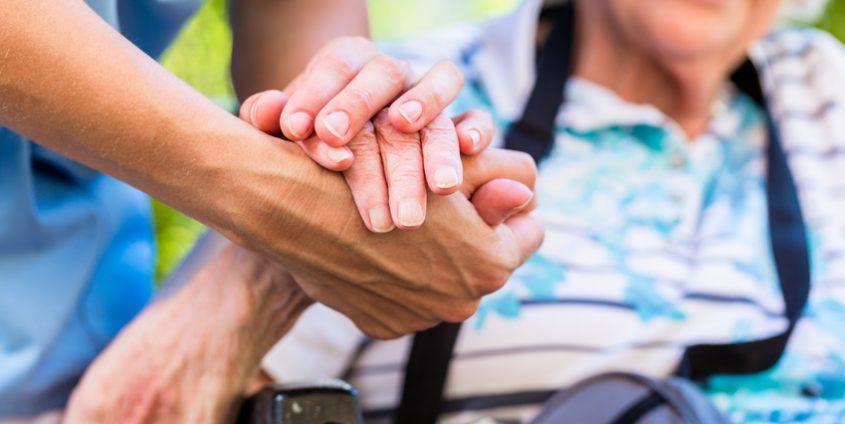 Die Hand einer älteren Dame in der Hand einer Pflegerin