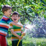 Cute little boy watering plants with watering hose in the garden.