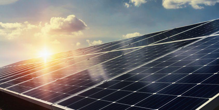 Photovoltaikmodule vor untergehender Sonne und Himmel mit Wolken