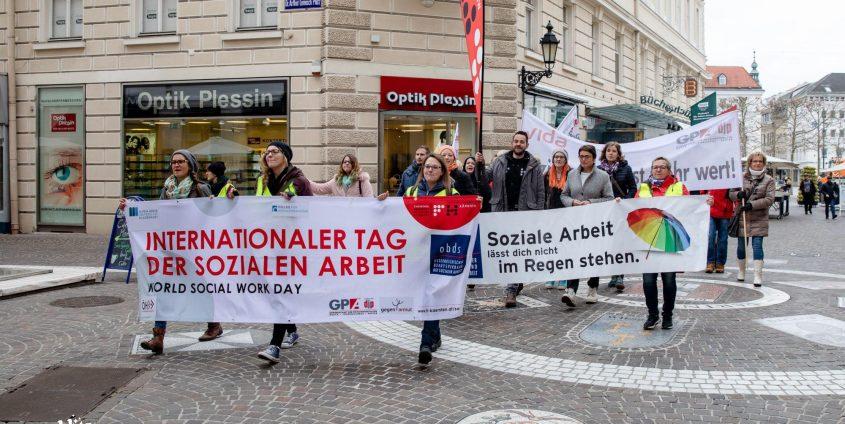 Foto: Gruppe von Menschen mit Transparenten zum Internationalen Tag der Sozialen Arbeit 2019