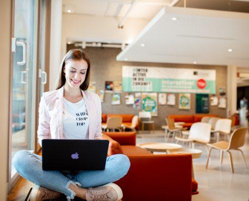 Studentin mit Laptop sitzt am Fenster in der Aula