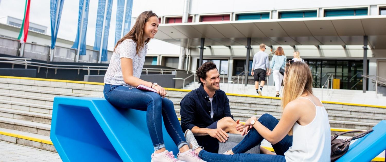 Gruppe von Studierenden sitzen vor dem Haupteingang der Universität Klagenfurt