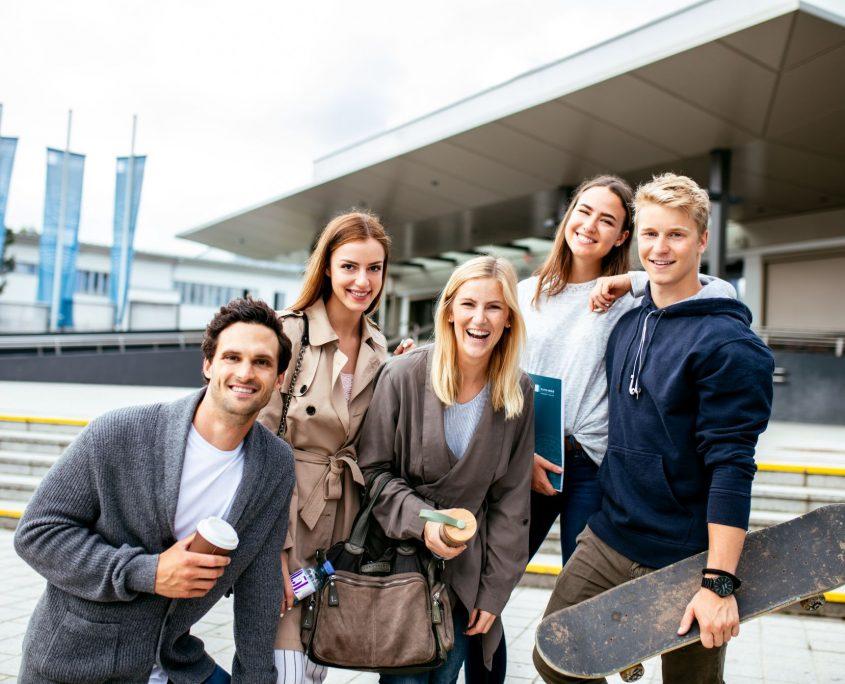 Gruppe von Studierenden vor dem Haupteingang der Universität Klagenfurt