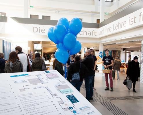 Tag der offenen Tür 2019 | Menschen und Luftballoons in der Aula