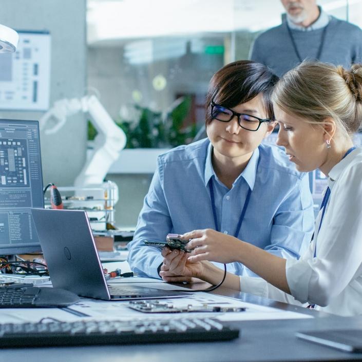 Wissenschaftlerinnen an ihrem Arbeitsplatz vor ihren Computer sitzend