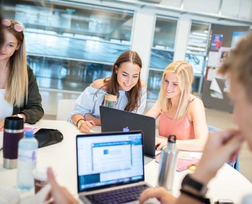 Studierende vor einem Laptop in der Aula