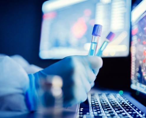 Ein Mensch in Schutzanzug sitzt vor einem Computer in einem Labor.
