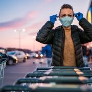 Frau mit Gesichtsmaske und Einkaufswagen