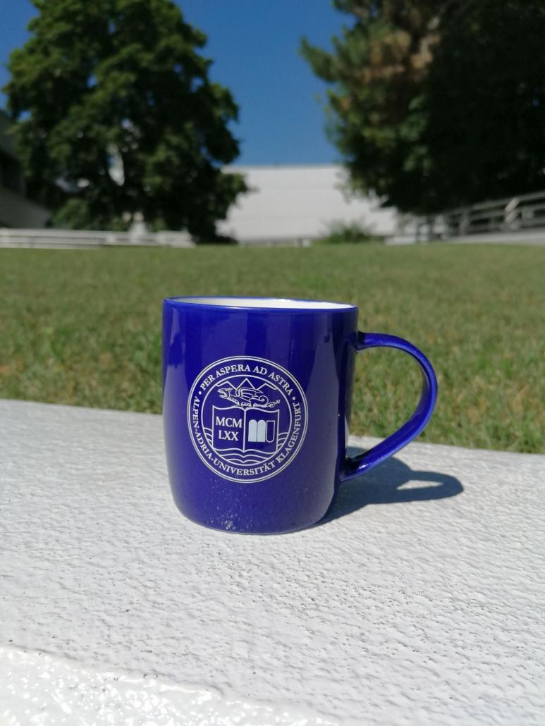 Foto von einer blauen Kaffeetasse in XL mit UNI Siegel, spülmaschinenfest auf der Mauer vor der Wiese im Bereich des Haupteingangs