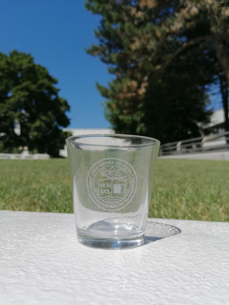 Foto von einem Wasserglas 0,2 L mit UNI Siegel auf der Mauer vor der Wiese im Bereich des Haupteingangs