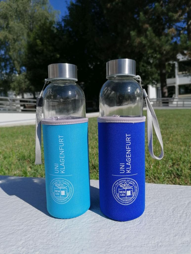Foto von zwei Glasflaschen mit Neoprenhülle in türkis oder dunkelblau mit 0,5 Litern Fassungsvermögen auf der Mauer vor der Weise im Bereich des Haupteingangs