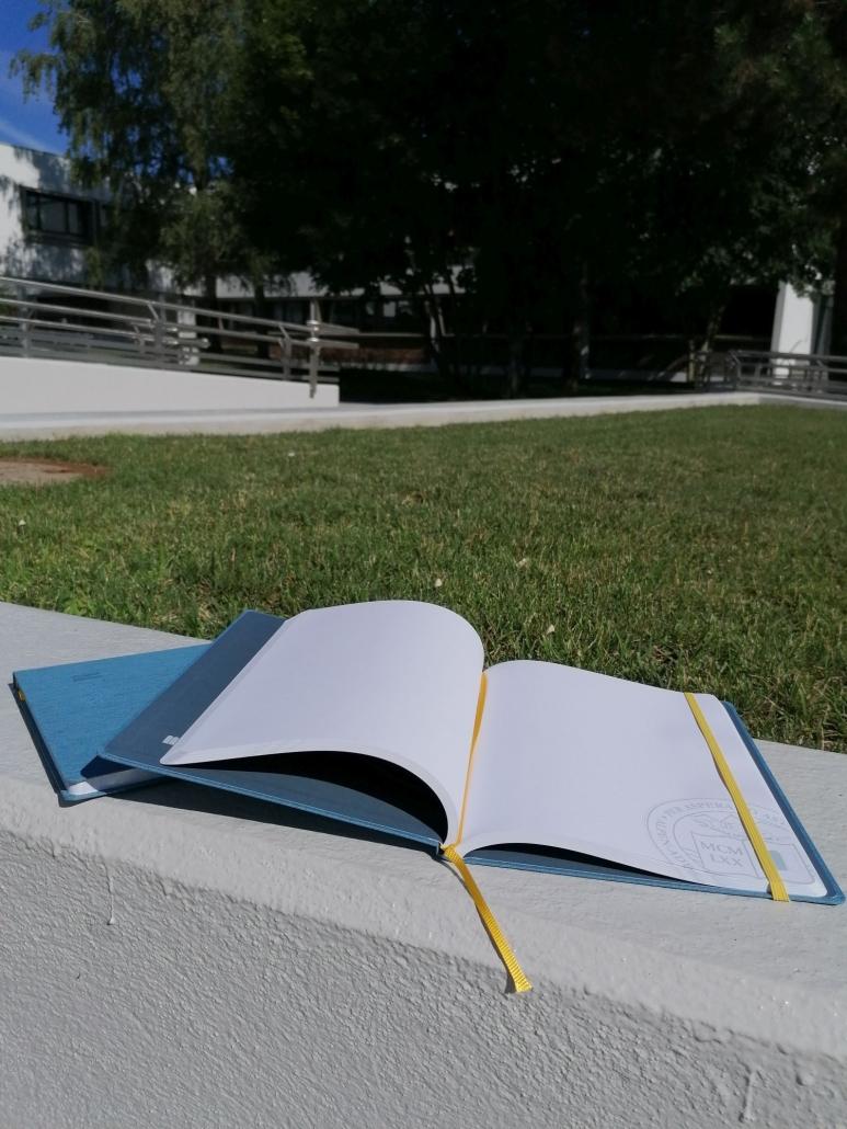 Foto von einem Notizbuch, 160 Seiten, 19 x 25 cm blauer Leineneinband mit Logoprägung, gelbes Lese- und Gummiband auf der Mauer vor der Wiese im Bereich des Haupteingangs