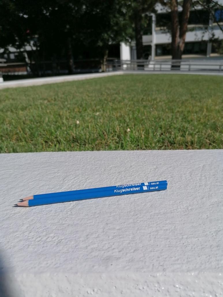 Foto von zwei Bleistiften au f der Mauer vor der Wiese im Bereich des Hauptgebäudes