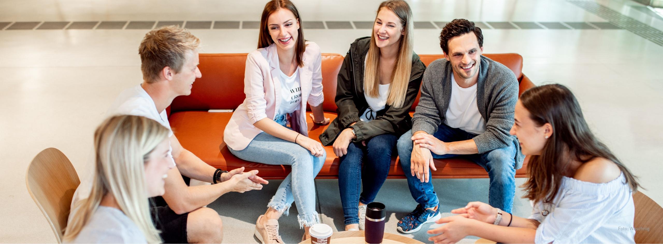Sechs Studierende sitzen auf einem Sofa und Stühlen in der Aula und trinken Kaffee.