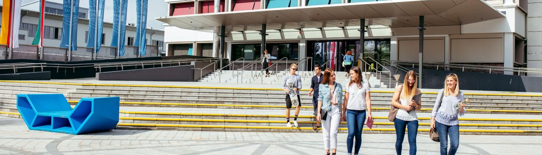 Studierende verlassen den Haupteingang der Universität