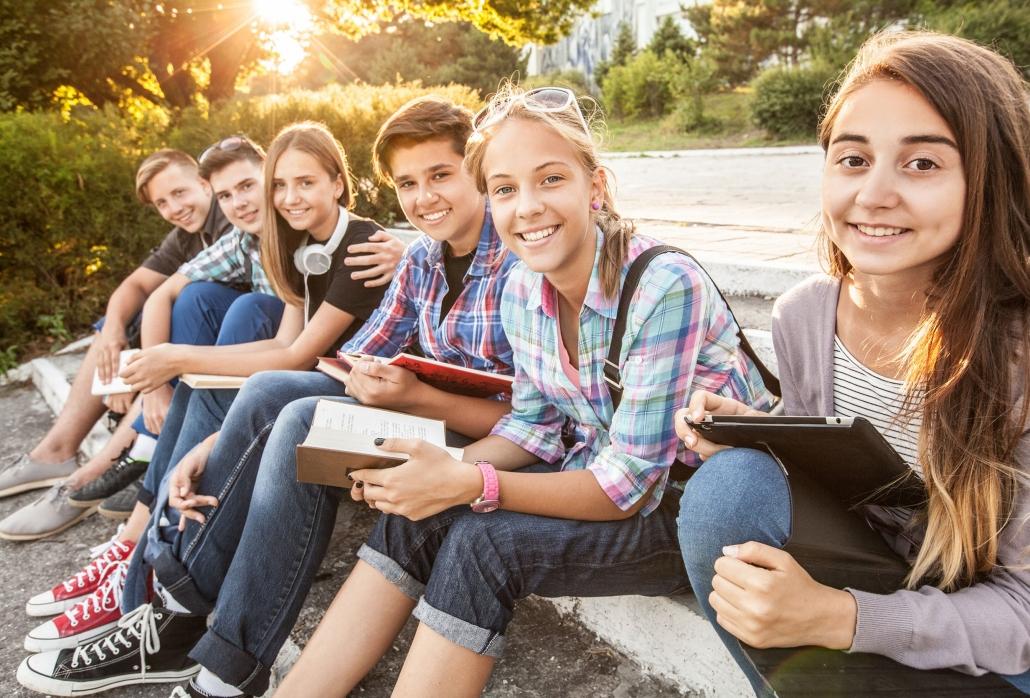 Gruppe von Jugendlichen sitzt auf einer Stiege im Park