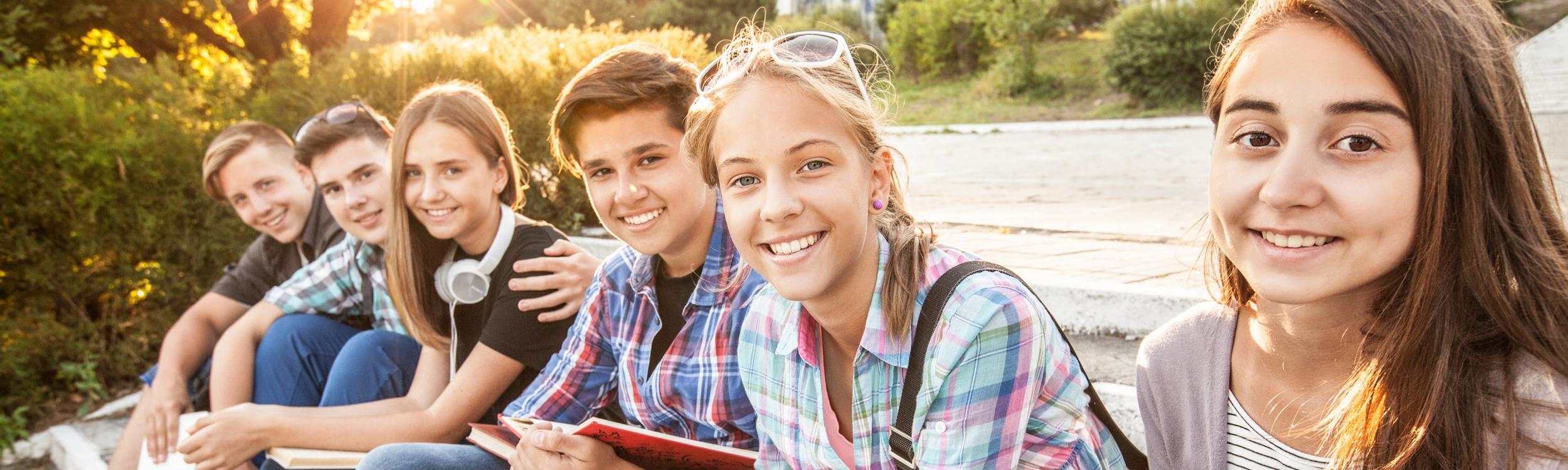 Eine Gruppe von Jugendlichen sitzt auf einer Stiege im Park.