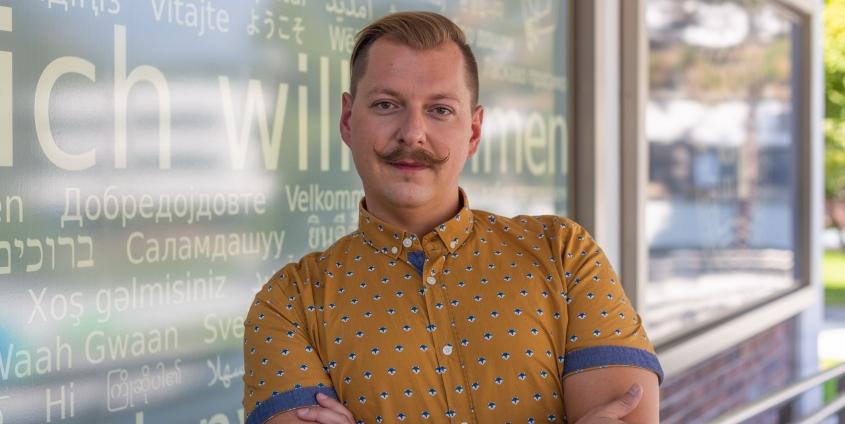 Michael Sikic Portraitfoto | Haupteingang Universität Klagenfurt | Willkommenstafel