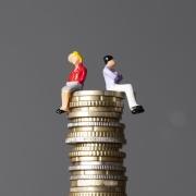 Zwei Figuren, ein Mann und eine Frau, sitzen auf einem Turm von Geldmünzen