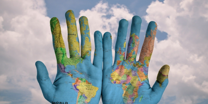 Hands with world map superimposed on them on a field of clouds