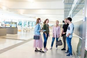Studierende in der Aula vorm Eingang in den Hörsaal