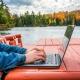 Jemand sitzt auf einer roten Sitzgarnitur an einem See und tippt auf einem Laptop