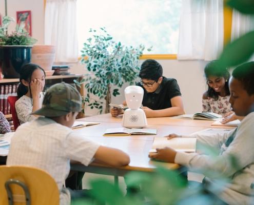 Avatar in Schulklasse, Kinder sitzen um den Mini-Roboter rundherum