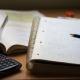 Block mit Mathematikaufgaben, Taschenrechner und Mathematikbuch