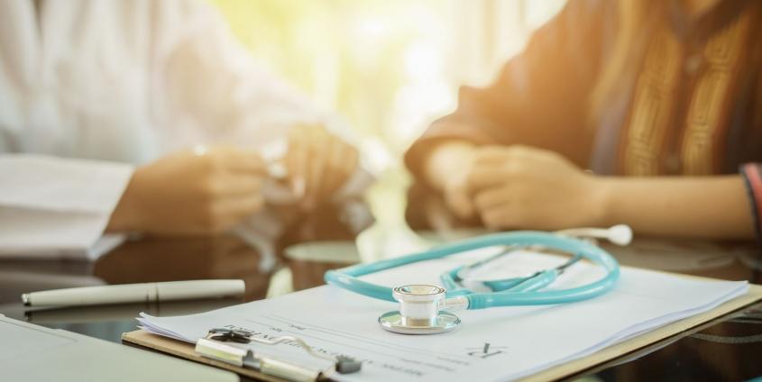 Klemmbrett mit Stethoskop im Vordergrund, Ärztin und Patientin im Hintergrund