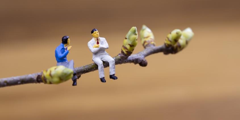 Zwei Figuren im Businessoutfit sitzen auf einem Zweig, der frischt austreibt