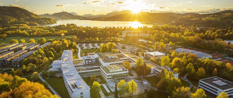 Luftaufnahme der Universität Klagenfurt mit dem Wörthersee im Hintergrund (gegen die Sonne fotografiert)