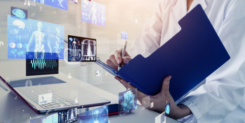 Gesundheitspersonal mit Krankenakte und digitalen Daten vor einem Laptop
