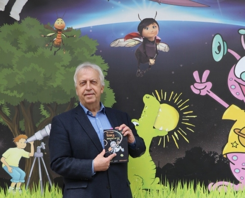 Harald Raffer in Uni-Nähe vor dem Planetarium mit seinem Jugendbuch