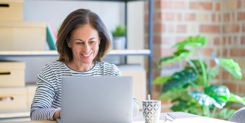 Eine Frau mittleren Alters sitzt lächelnd vor einem Laptop