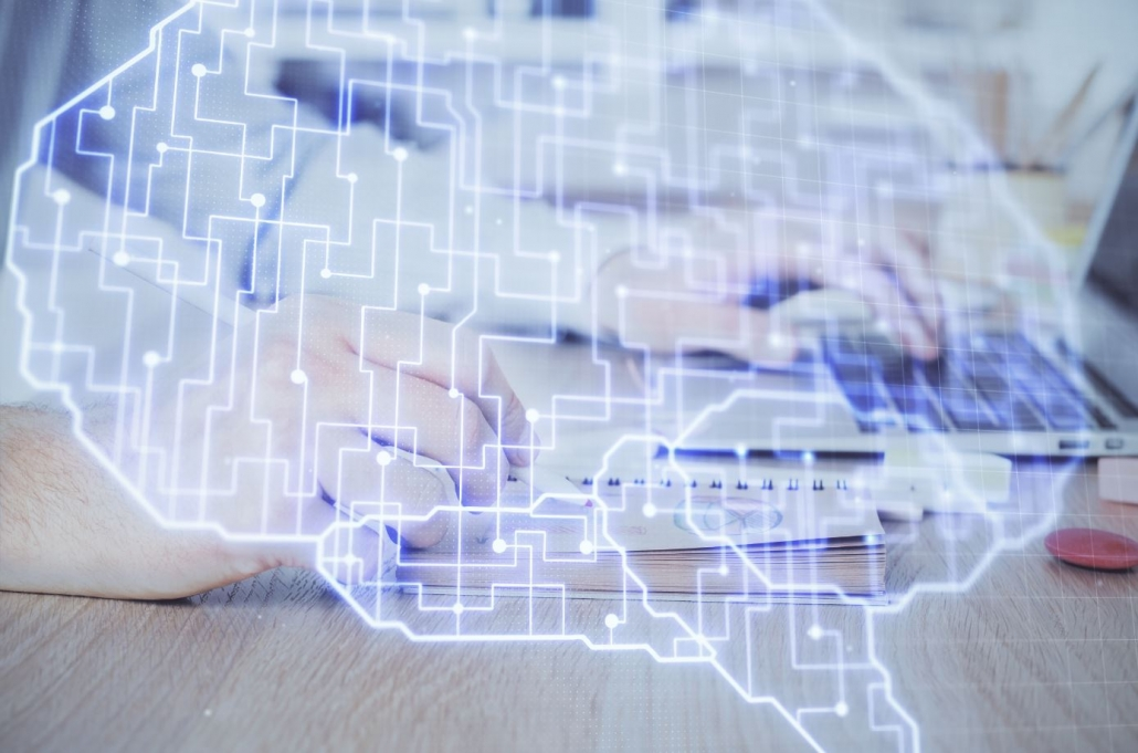 Hologramm eines Gehirns, im Hintergrund sitzt jemand an einem Schreibtisch mit Laptop