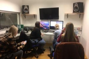 Studierende arbeiten im Medienlabor an Bildschirmen.