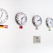 CD-Labor: Uhren zeigen die verschiedenen Zeitzonen der Herkunftsländer der Mitarbeiter*innen an